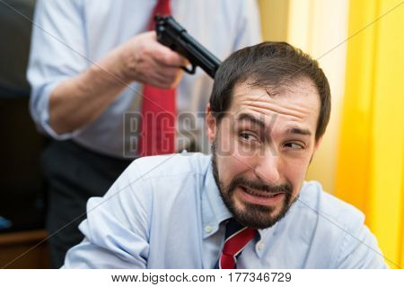 Businessman pointing his gun to a colleague's head