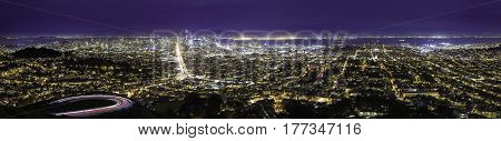 City view at night of San Francisco. The aerial skyline shows both the financial district or downtown metropolis as well as urban residential housing in Oakland and SF. The image depicts tourism in America.