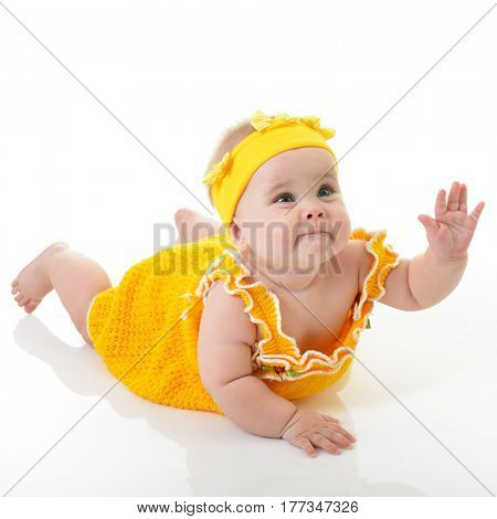 Adorable baby girl reaching for something, studio short over white background. Portrait of cute child. Beautiful little girl.