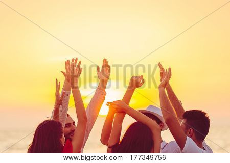 people dancing at the beach with hands up. concept about party, music and people.