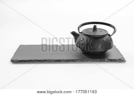 Cast-iron black teapot located on rectangulat shale plate on white background