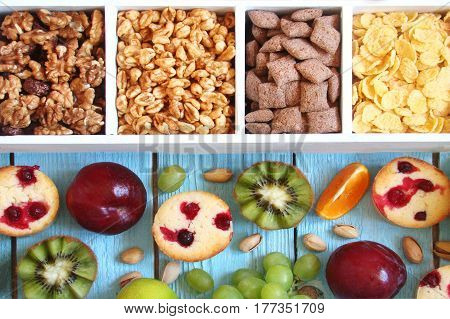 Breakfast for children multigrain flakes puffs rings popcorn in a wooden box and muffins with fruits on a blue background