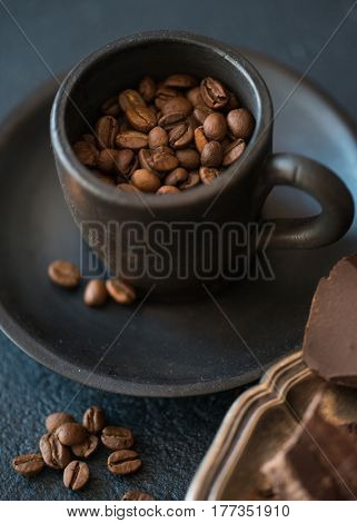 Cup with coffee beans and pieces of bittersweet dark chocolate