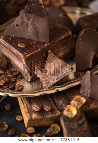 Pieces of bittersweet dark chocolate spread out on a wooden background