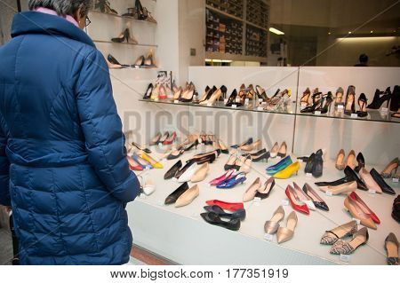 Adult woman looking at shoes in a shop window