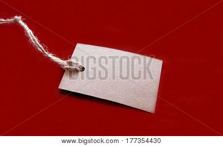 Blank tag tied with string on red background. Price tag label sale tag