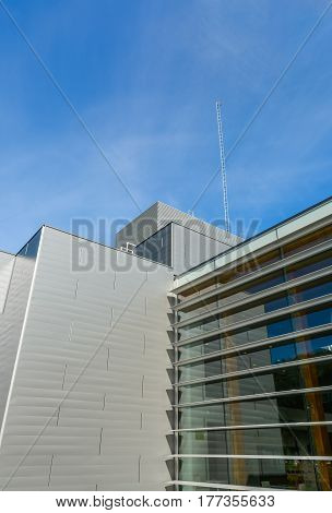 Modern urban building on cloudy sky background. Business office building with mast and antenna on the roof