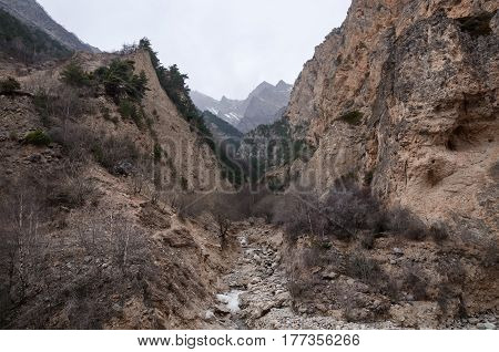 A stormy river flows in a narrow, mountain gorge in cloudy weather