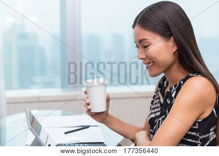 Businesswoman drinking coffee using laptop at office desk. Asian woman working on computer online at home.