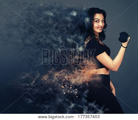 Dispersion effect .Beautiful girl holding a dumbbell