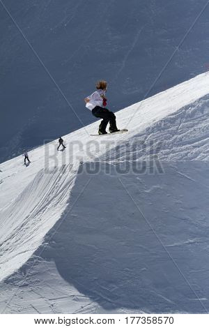 SOCHI, RUSSIA - MARCH 22, 2014: Snowboarder jumps in Snow Park, ski resort