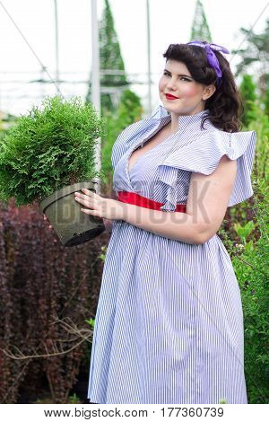 Young beautiful plus size Girl keeps pot with plant in the garden. Girl among the plants in the garden.