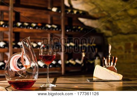 Wine carafe, wine glass and cheese placed on the wooden table in a wine vault.
