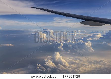 Airplane wing against a background of clouds. View from the window.