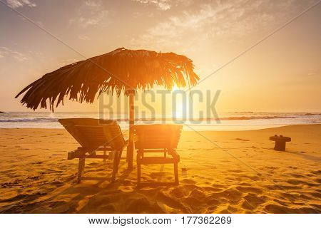 Chaises longues on the beach at sunset