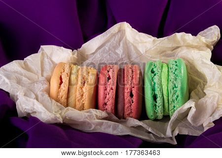 Tower Of Three Colorful Macaroons On Purple Background. French Dessert.