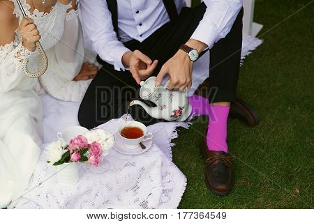 Bride and groom drink tea in bright clothes on the green grass