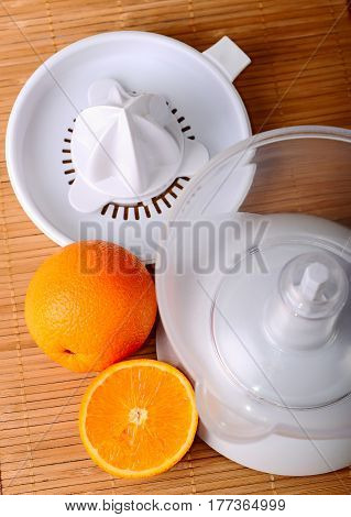 The fruit juicer and oranges on mat, high view angle