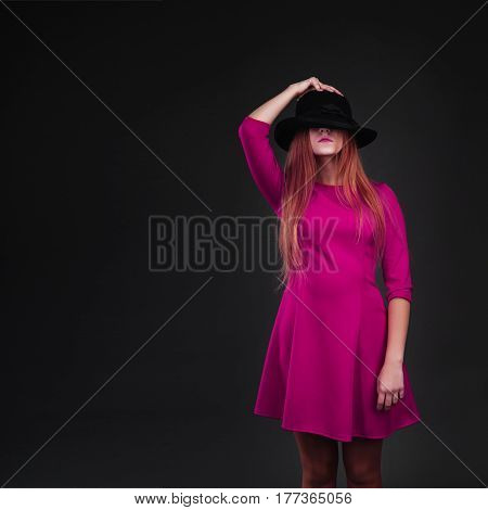 A beautiful girl dressed in crimson holding her hat. Girl holding hat up to face