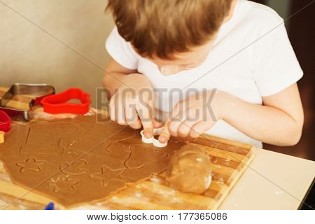 Children's hands make gingerbread. Small boy cutting cookies for Christmas. Kid Baking Cooking Cookies Fun Concept. Master class for children on baking christmas gingerbread.