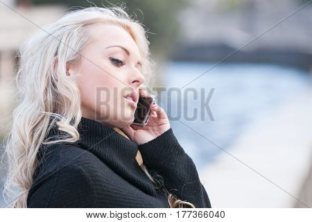 Stern Beautiful Woman On The Phone Outdoors