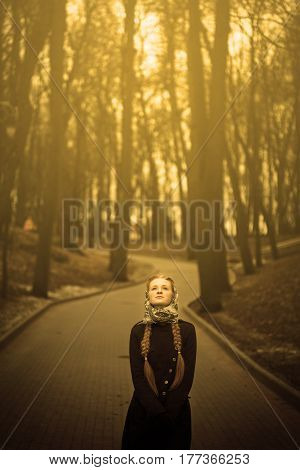 Beautiful red-haired girl lonely standing on the road.