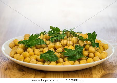 Chickpeas and parsley. Plate of cooked chick peas and leaves of fresh parsley on a plate on wooden table background
