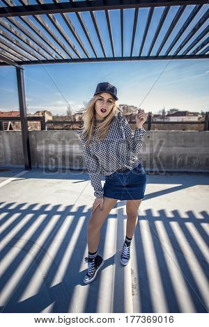 Woman Street Style Posing, Wearing Checkered Shirt, Denim Skirt, Leather Cap And Classic Sneakers