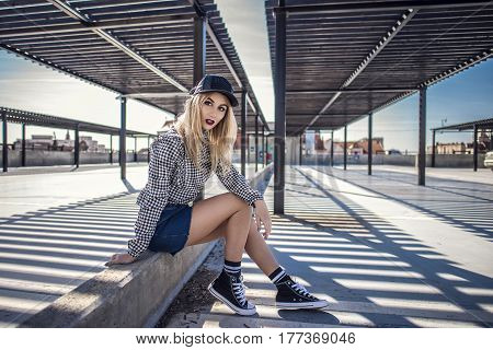 Fashion Hipster Woman Sitting On Concrete Wall Wearing Sneakers