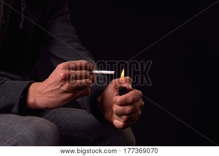 Close Up Of A Teenager Hands Holding A Cigarette And O Lighter, Ready To Light It. Studio Photo. Har