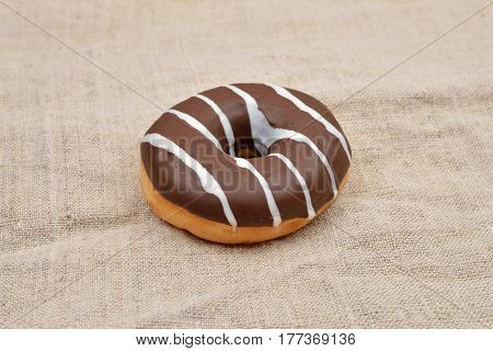 Chocolate donut with stripes on a jude background. Sweets. Selective focus