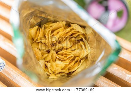 potato crisps in bag on wooden bench outdoor.