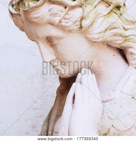Figure of a praying angel as a symbol of Christianity (Religion faith sin salvation concept)