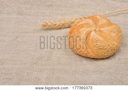 Freshly Baked Whole Grain Round Sandwich Bun Sprinkled With Sesame Seeds With Ears Of Wheat Near On