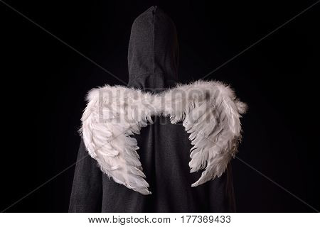 Back Of A Young Man With Black Hoodie And White Feathered Wings Behind The Back On A Dark Background
