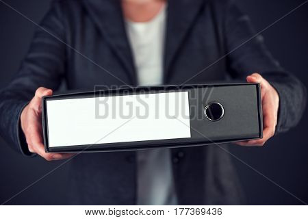 Businesswoman holding document ring binder with blank label as copy space female accountant or financial advisor archiving business documentation