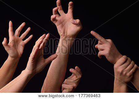 Many Desperate Female And Male Hands Elevated Into The Air Trying To Reach Or Grab Something On A Bl