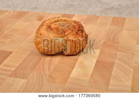 Homemade Roll Of Puff Pastry With Nuts On Wooden Background. Sweet Pastry. Selective Focus