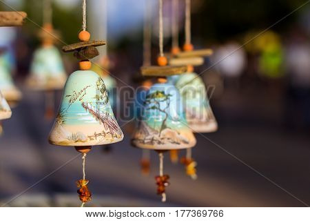 Palanga Lithuania - August 9 2012: Souvenir decorative bells with image of Palanga bridge on tongue of bell dangling amber stones. Tourist Souvenirs for memorable shopping. Klaipeda County
