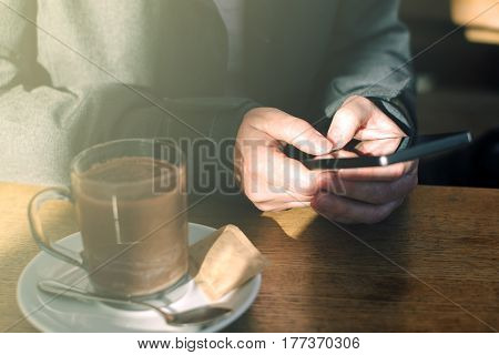 Woman using mobile phone and drinking hot chocolate in cafe. Casual young adult caucasian female behind the glass typing text message on smartphone app.
