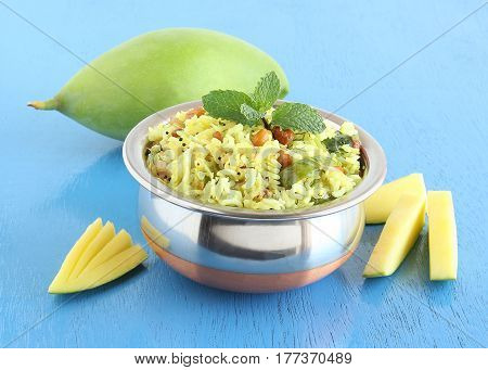 Mango rice, Indian vegetarian food, made a variety of raw mango known as Totapuri, which is in the background.