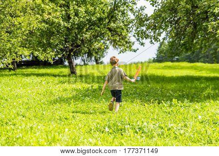 Young boy running away on garden background.