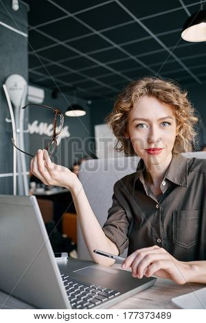 joyful smiling woman sitting in a cafe near the open laptop at a table made of wood . in the background a bright window with bright daylight. Woman boss looks appraisingly. job Interview or business concept
