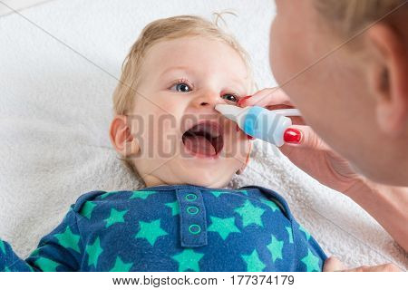 Mother cleans the baby's nose with a blower while the infant is lying and smiling.