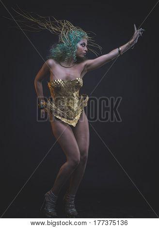 Virgin, Latin woman with green hair and gold tiara, wears a handmade warrior armor