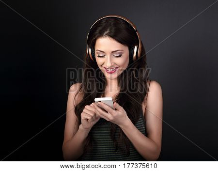 Beautiful Calm Young Woman Listening The Music In Wireless Headphone From Mobile Phone And Smiling O