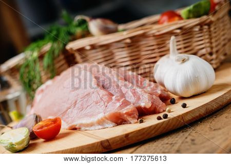 Slices of raw pork meat and wicker basket with vegetables