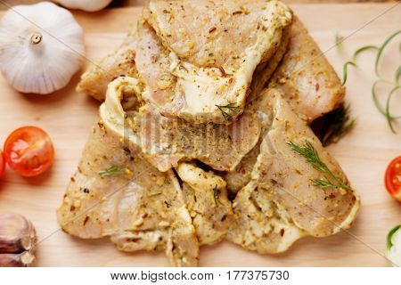 Raw marinated pork meat and vegetables on a wooden background