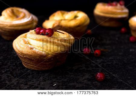 A bun on a porcelain saucer with berries and sauce. Dark grunge background. Mystical light.