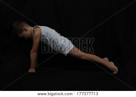 sport time. Young active caucasian white boy doing gymnastics isolsted on black background.a todler doing exercises for muscles.